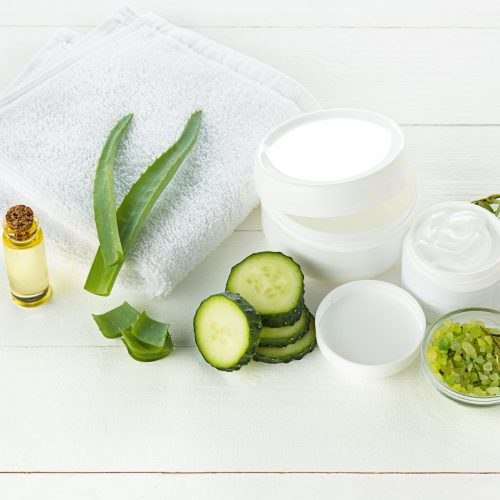 Cucumber and aloe cosmetic cream face, skin and body care hygiene moisture lotion and wellness therapy mask in glass jar with towel on white background